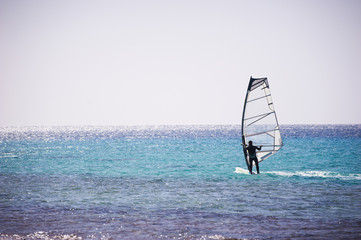 Windsurfing sail on the blue sea