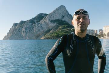 Diver in wet suit standing on beach