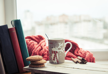 Cup of coffee or tea, smartphone and earbuds with autumn leaves near a window. Autumn playlist concept. Autumn music for rainy days.