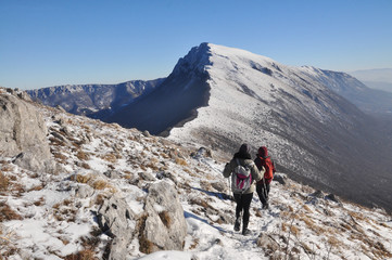 Couple of mountaineers hiking on snowy mountain into the sun. Climbers high in snowy mountains
