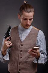 Gangster with a gun looks into the phone on a gray background