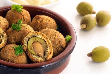 baked olives in a dough coat with parmesan cheese, party finger food, spanish tapas appetizer in a typical brown ceramic bowl on a white table, close up