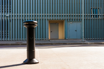 The ashtray on sidewalk on the background of facade of the urban parking building with steel panels in a row, Saint Petersburg, Russia