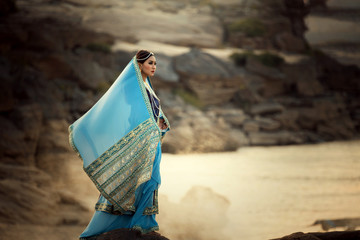 Portrait woman wearing Iran or Arab traditional dress standing on sand riverside