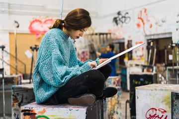 Woman creating drawing in studio