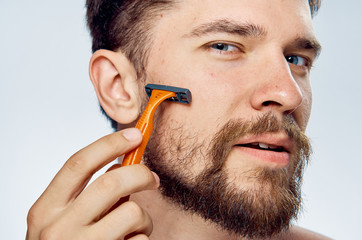 Man with a beard on a light background shaves with a razor, portrait