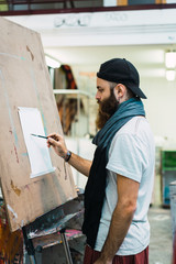 Bearded man drawing on easel
