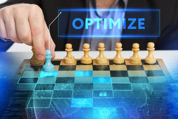 The concept of business, technology, the Internet and the network. A young entrepreneur working on a virtual screen of the future and sees the inscription: Optimize