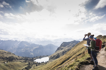 Germany, Bavaria, Oberstdorf, two hikers with map and binoculars in alpine scenery