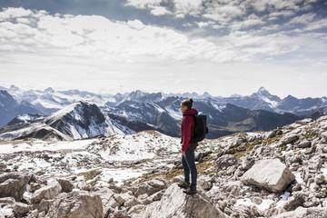 Germany, Bavaria, Oberstdorf, woman standing on rock in alpine scenery