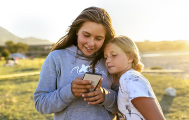 Asturias, Spain, teenage girl showing photos to her sister with a smartphone