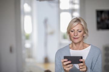 Portrait of senior woman at home looking at cell phone