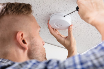 Person's Hand Using Screwdriver To Install Smoke Detector