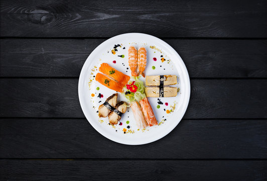 Sashimi set on a white round plate, decorated with small flowers, Japanese food, top view. Black wooden background