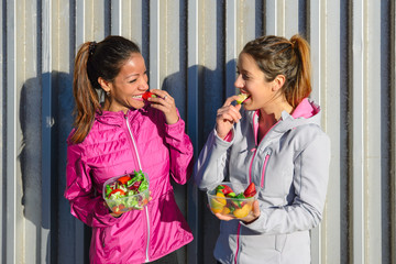 Two sporty women on fitness diet eating a healthy green salad with fruits after exercising.