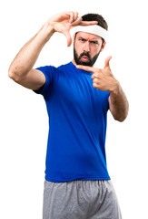 Funny sportsman focusing with his fingers on isolated white background
