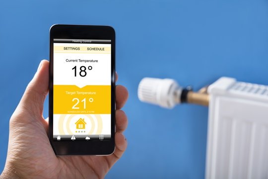 Person Hand Setting Temperature Of Thermostat Using Mobilephone