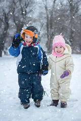 Little boy and girl waving hands outdoors during snowy winter day.