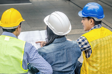 Back view of Asian young foreman and engineer checking the blueprint and talking about construction project with commitment to success at construction site.
