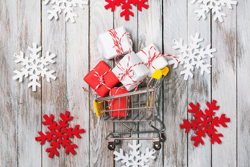 Christmas gift boxes in shopping cart on a wooden background with decorations around, top view. Christmas sale concept.