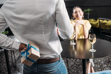 cropped shot of man hiding gift for girlfriend behind back