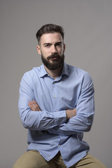 Young grumpy pessimistic bearded business man with crossed arms sitting and looking at camera against gray studio background.