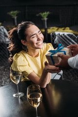 excited asian woman receiving anniversary gift from boyfriend