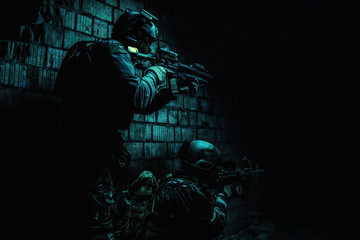 Pair of soldiers in action under cover of darkness low angle