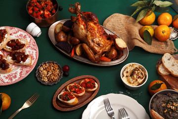 Traditional dinner with roasted chicken, pate and tomato bruschettas on dark green background. Overhead view. Family dinner concept.