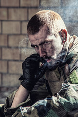 Handsome soldier sitting in ruined building smoking cigarette staring at the camera