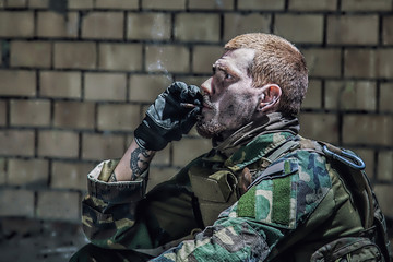 Special forces soldier after the fight sitting in ruined building smoking cigarette staring at the camera