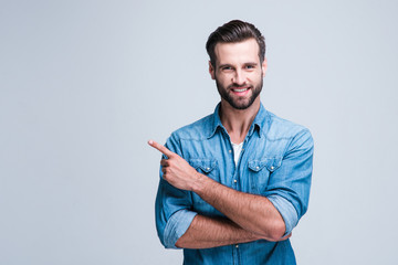 Have you seen this? Handsome young man pointing away and looking at camera with smile while standing against white background Wall mural