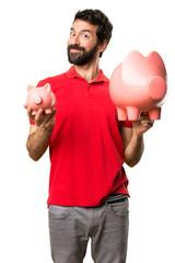 Happy Handsome man holding a piggybank