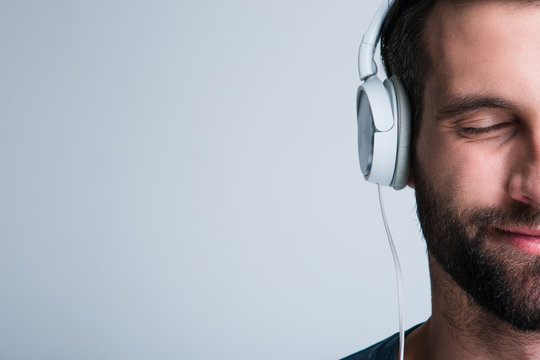 Perfect song. Part of portrait of handsome young man listening to music in headphones with smile while standing against white background