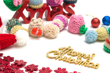 X-mas and merry christmas text, ball, fur hat, red snow flower decoration on white background