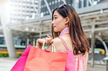 Portrait of woman walking with shopping bags at city background. Back view