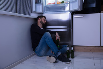 Man Sitting On Floor Drinking Beer