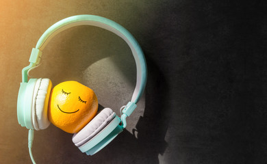 Relaxing in Summer with Music Concept, present by Orange Fruit Listening in Headphone, Happy Smiley Face Drawn on Skin