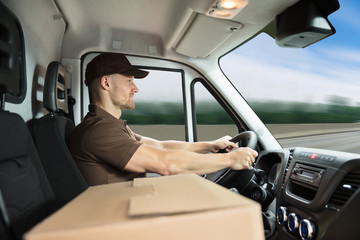 Delivery Man Sitting Inside Van With Cardboard Box