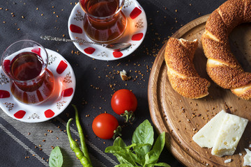Fresh bagel sandwich with turkish tea on chopping board