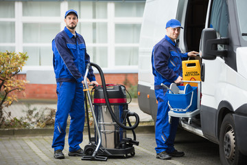 Two Male Janitor Unloading Cleaning Equipment From Vehicle