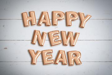 """Luftballons formen den Spruch """"Happy New Year"""" auf Holzuntergrund"""