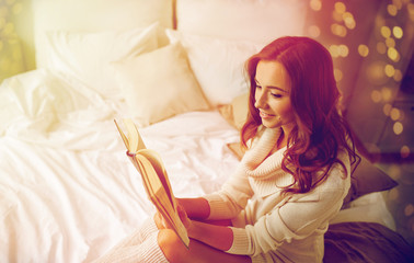 Fototapete - happy young woman reading book in bed at home