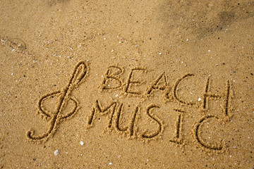 Music key and text beach music drawn on a yellow sand.