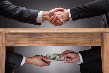 Businesspeople Shaking Hands And Taking Bribe Under Table