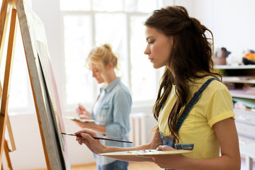 woman with easel painting at art school studio