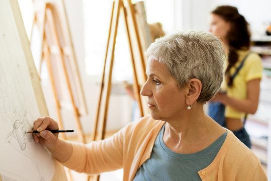 senior woman drawing on easel at art school studio