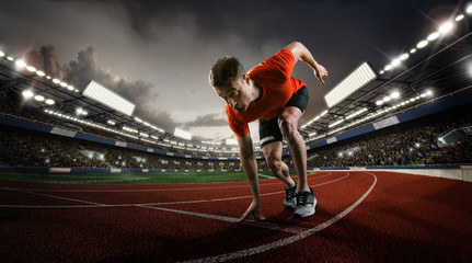 Sport backgrounds. Sprinter starting on the sport arena. Dramatic image.