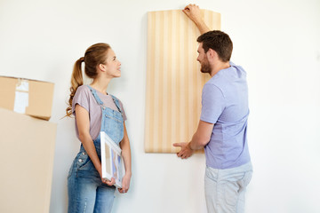 couple with wallpaper repairing apartment or home