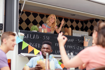 happy saleswoman showing thumbs up at food truck